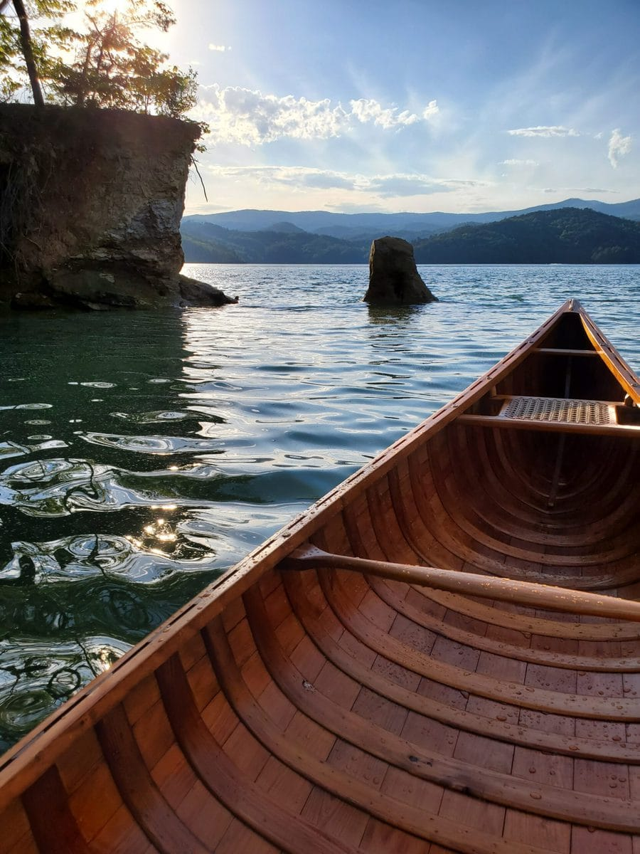 A photo of the Horace Strong canoe, taken at sunset from someone sitting inside the canoe, the view is of the lake. In the background is an island and mountains.