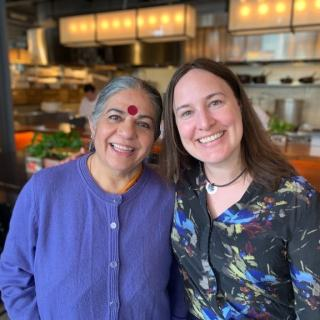 Ashley is wearing a blue and gray floral sweater and standing with Dr. Vandana Shiva