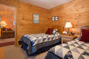 2 twin beds in bedroom of 2 bedroom cabin with floral quilts