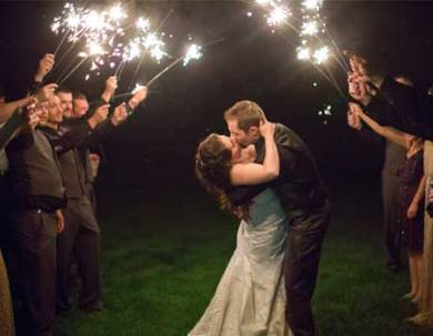 Wedding couple kissing under sparklers at sterling ridge