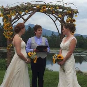 wedding couple under the arbor at large pond | Sterling Ridge Resort