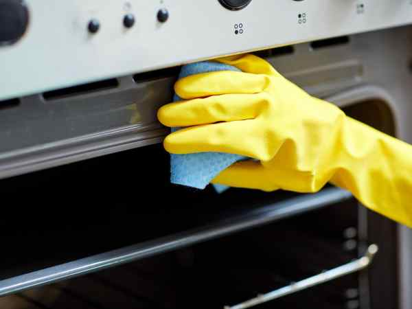 people, housework and housekeeping concept – close up of woman hand in protective glove with rag cleaning oven at home kitchen
