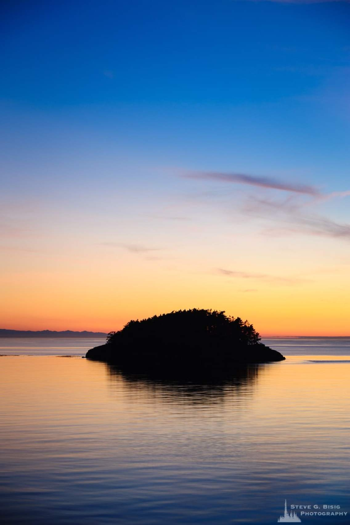 A landscape photograph of the August sunset over Deception Island at Deception Pass State Park, Washington.