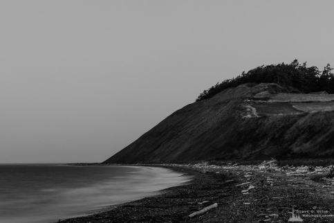 A black and white, long exposure photograph of the pre-dawn darkness along the shoreline of Ebey's Landing on Whidbey Island near Coupeville, Washington.