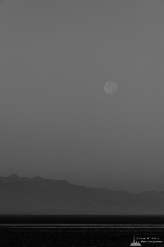 A black and white photograph of the setting full moon on an August morning over Admiralty Inlet as viewed from Ebey's Landing on Whidbey Island near Coupeville, Washington.