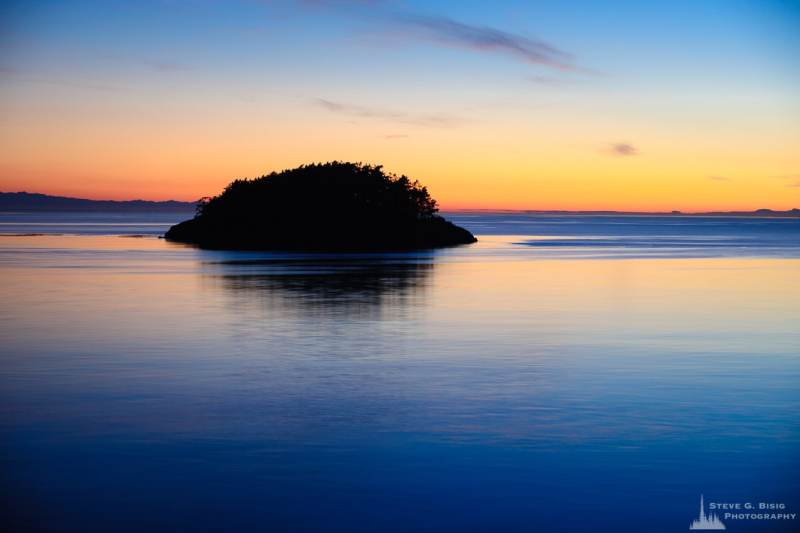 A landscape photograph of the setting sun over Deception Island at Deception Pass State Park, Washington.