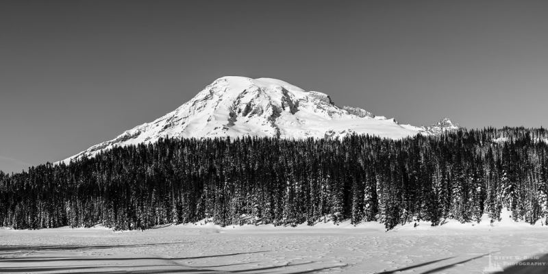 A panoramic black and white landscape photograph of a snow covered Reflection Lake below Mount Rainier along the Stevens Canyon Road at Mount Rainier National Park, Washington.