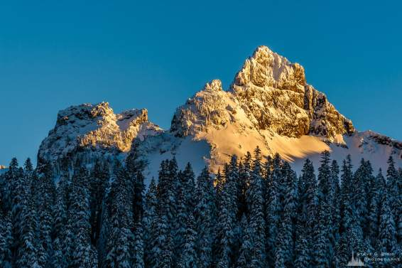 A landscape photograph of the last rays of the winter sunlight (alpenglow) shining on a snow covered Pinnacle Peak as captured along the Paradise Road at Mount Rainier National Park, Washington.