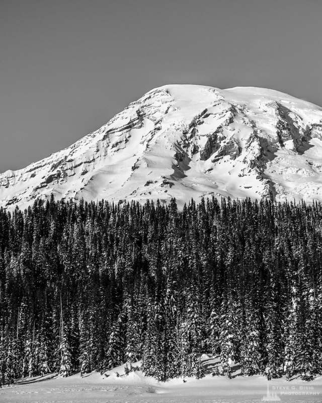 A black and white landscape photograph of Mount Rainier as viewed from a snow covered Reflection Lake at Mount Rainier National Park, Washington.