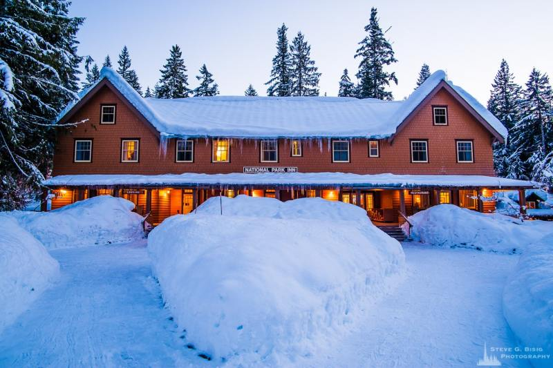 A photograph of the historic National Park Inn at dusk during the winter at Longmire, Mount Rainier National Park, Washington.
