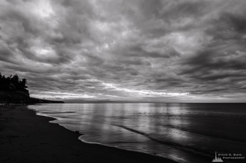 A black and white long exposure landscape photograph of cloudy early autumn skies captured along West Beach on Whidbey Island, Washington.