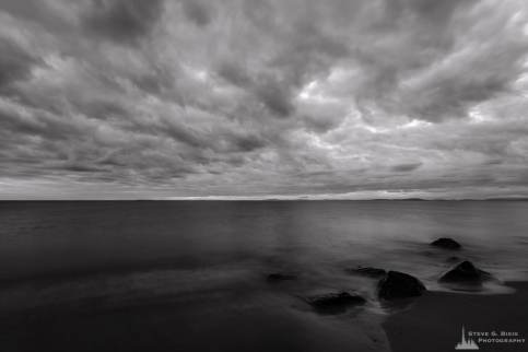 A black and white landscape photograph of cloudy early autumn skies captured along West Beach on Whidbey Island, Washington.