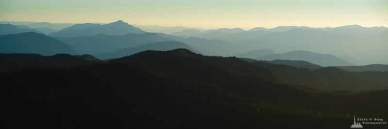 A panoramic landscape photograph of the distant hazy ridges as viewed from the Glacier View Lookout near Ashford, Washington.