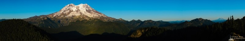A panoramic landscape photograph of Mount Rainier (and Mount Adams in the distance) as viewed from the Glacier View Lookout near Ashford, Washington.
