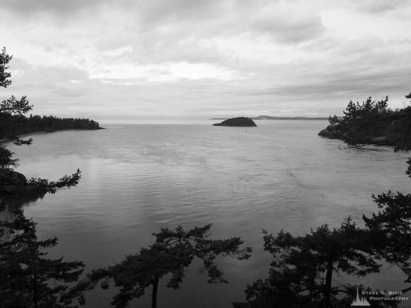 A black and white mobile landscape photograph of the waters of Deception Pass as viewed from Goose Rock on Whidbey Island at the Deception Pass State Park, Washington.