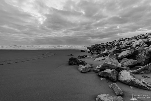 A black and white landscape photograph of the Pacific Ocean and beach along the South Jetty of Grays Harbor at Westhaven State Park near Westport, Washington.