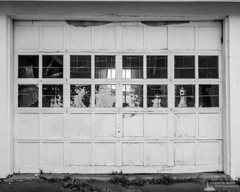 A black and white mobile urban photograph of an old roll-up door on a vacant building in Oak Harbor, Washington.