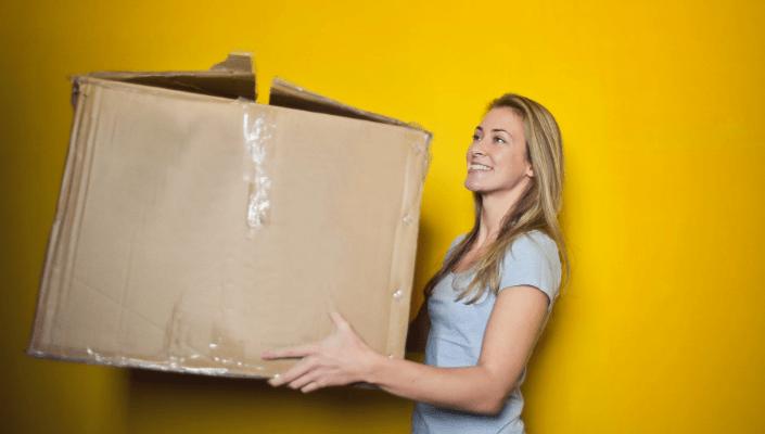 a woman holding a big box