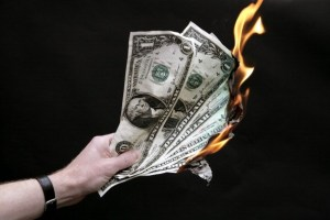 GERMANY - OCTOBER 07: GERMANY, BONN, Financial crisis - hand holds burning dollar notes. (Photo by Ulrich Baumgarten via Getty Images)