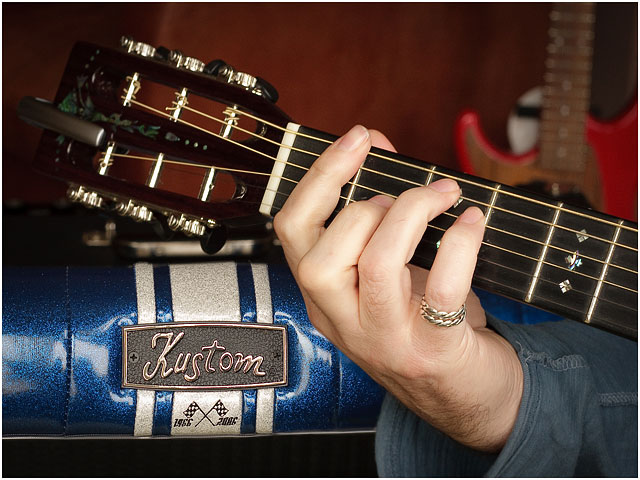 Close Up Of Guitarist With Hand On Guitar Fretboard With Amplifier in Background