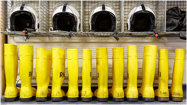 RNLI Portsmouth Lifeboat Station Yellow Boots And Safety Helmets in Crew Room