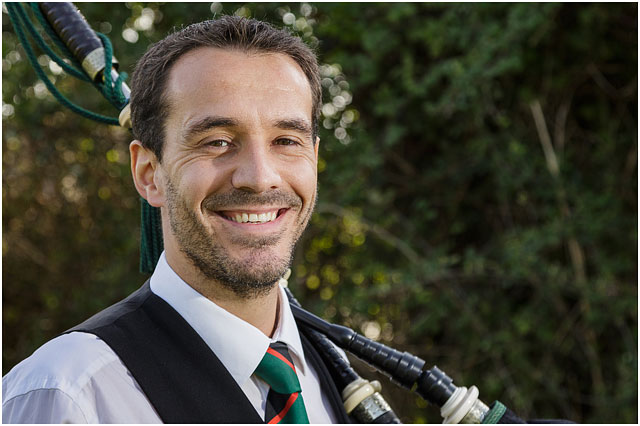 Portrait Of Male Bagpiper Standing Against Green Foliage Holding Bagpipes