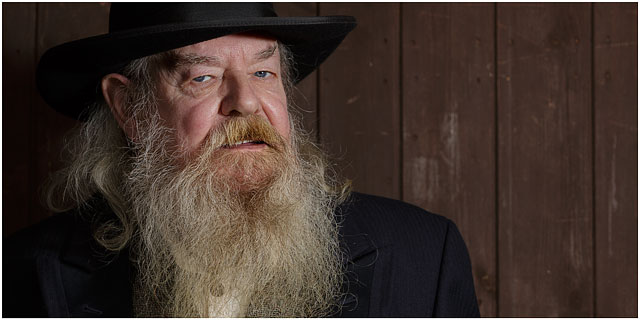 Portrait Of Wild West Preacher With Black Hat And White Bushy Beard Looking Towards Camera