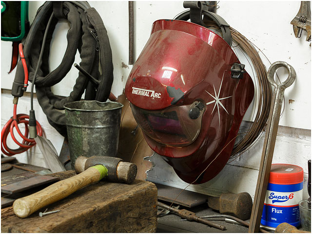 Blacksmiths Workshop Red Welding Helmet And Tools Hanging On Wall