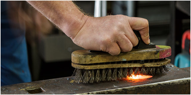 Removing Excess Scale On Red Hot Poker On A Blacksmiths Anvil With Wire Brush