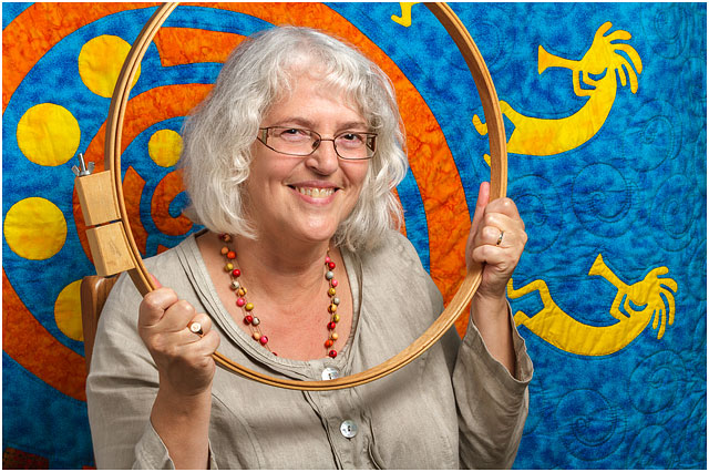 Headshot Portrait Of Textile Artist Framed By Wooden Quilting Hoop