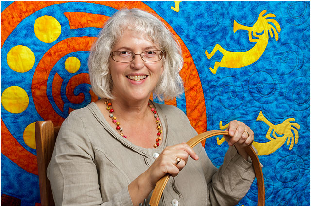 Headshot Portrait Of Textile Artist Holding Wooden Quilting Hoop In Front of Quilted Kokopelli Figures