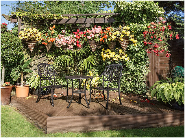 Wooden Pergola Decking Metal Table Chairs Hanging Baskets Red Yellow Pink Flowers Green Foliage Blue Sky