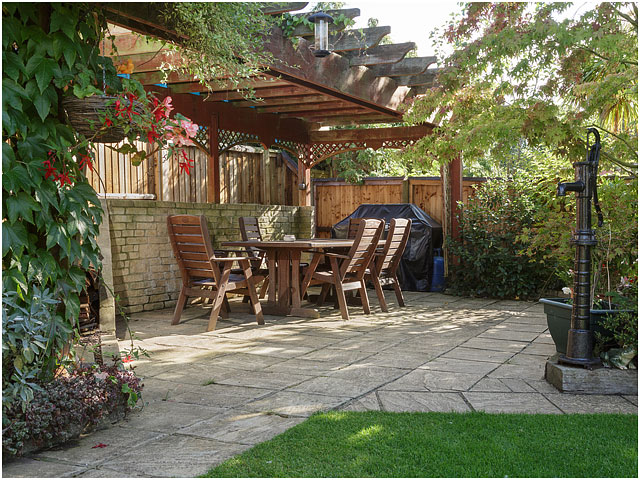 Wide View Wooden Garden Furniture Table Chairs Dappled Shade Paving Pergola Foliage