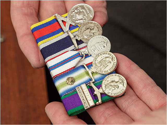 A selection of mounted medals held in the hand