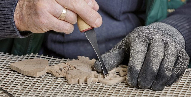 close up of male woodcarver and intricate carving