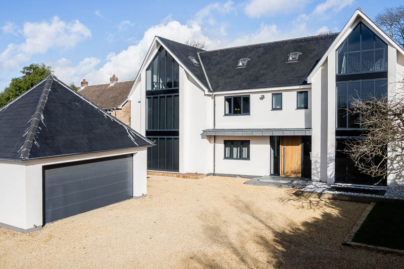 Elevated view of a bespoke self build house with white facing and slate roof