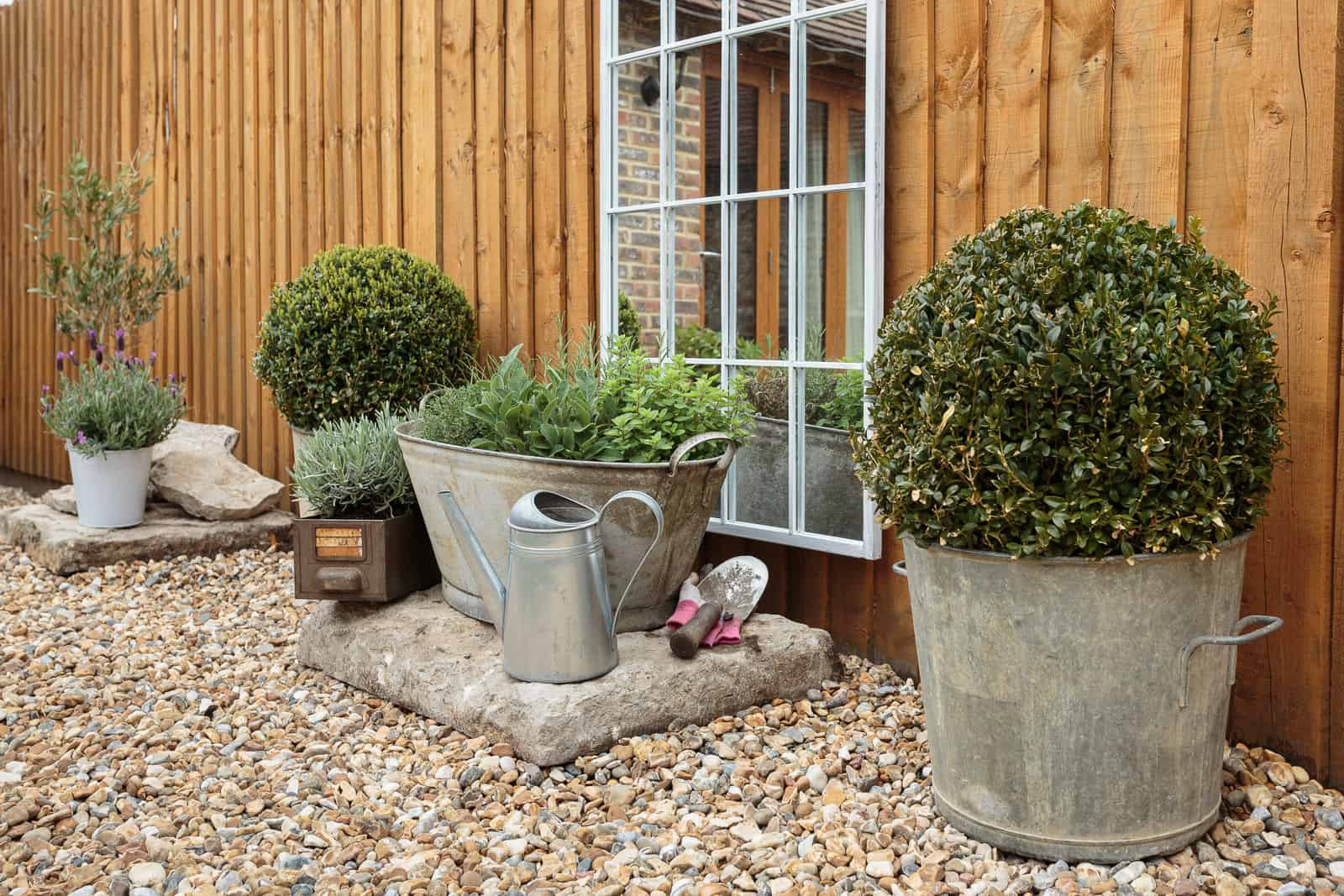 Ornamental bushes and plants in tin baths and containers on a shingle base