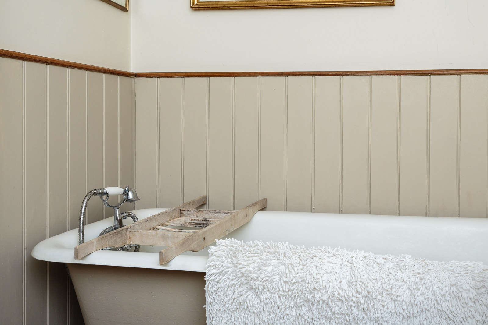 freestanding roll top bath in period bathroom with wooden panels on wall