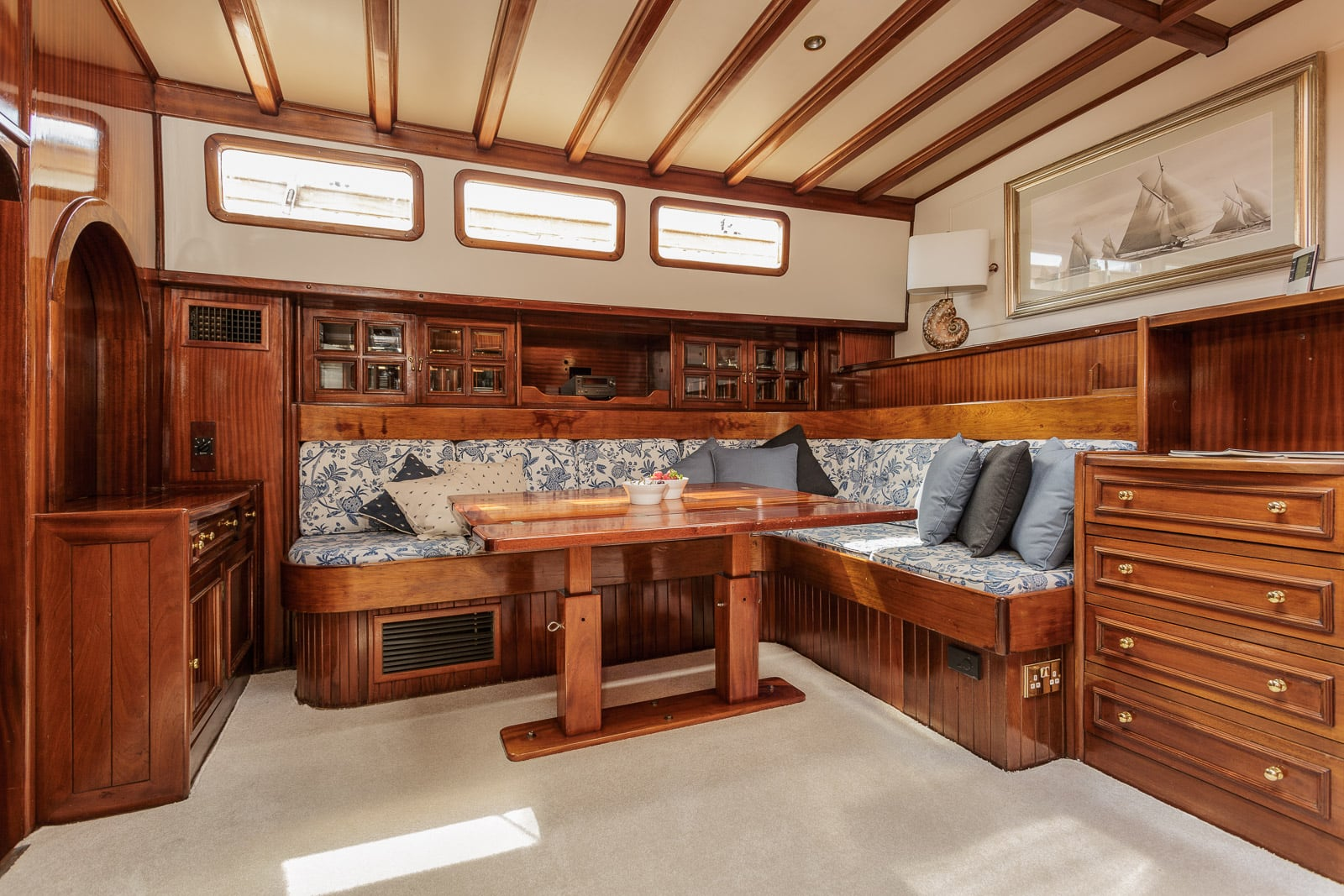 Below deck view of a wooden schooner yacht with adjustable height table, seating and plan chest fashioned in dark wood throughout