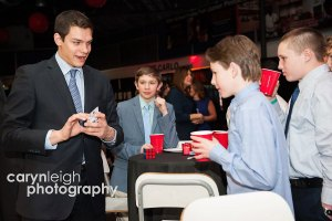 Magician Steven Brundage performs a card trick for a group of boys