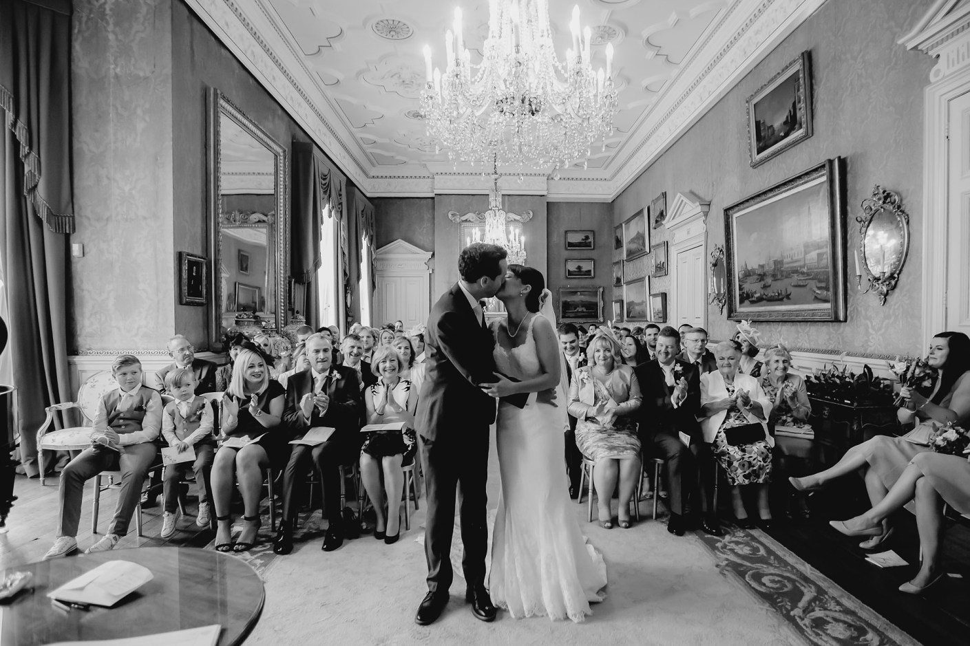 wide anle photo of the kiss at the wedding