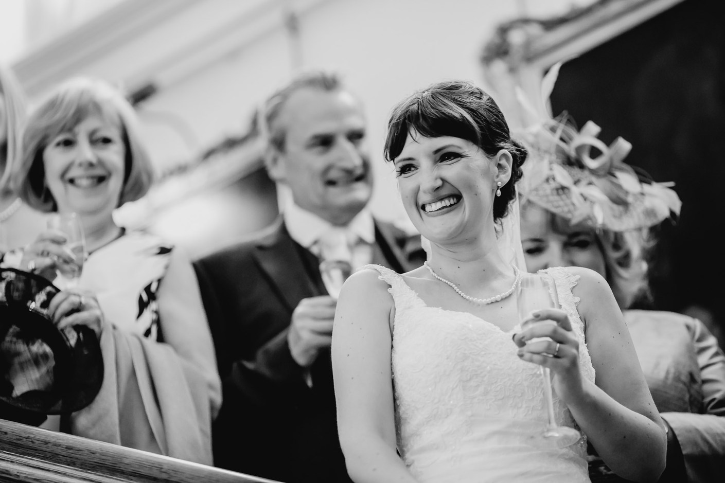 bride laughing during the speeches on the staircase - capesthorne-hall-wedding-photographer