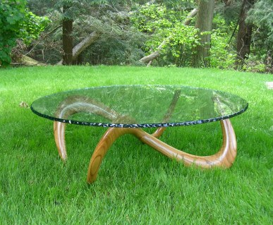 """Infinity table made from curly red oak with """"bark"""" edging to the glass that is also polished"""