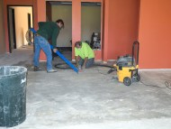 "Keith, left, and Paul from ""All States Flooring"" in Fargo prepare the concrete for new flooring"