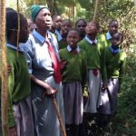 Kenyan grandmother at school with her great-great-grandchildren