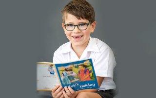 A primary school boy reads a book