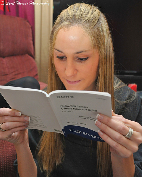 A young woman reading her new digital camera's manual.