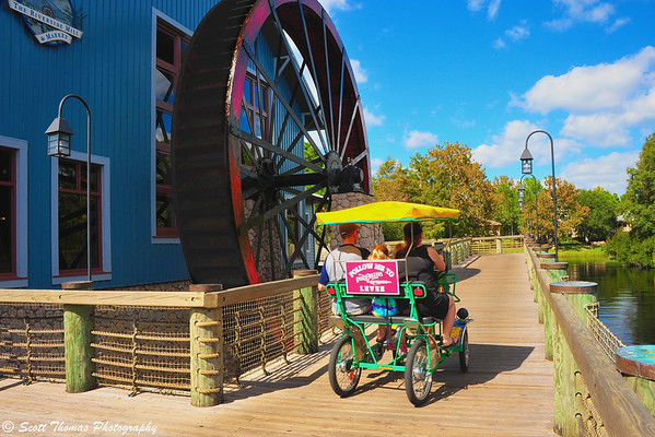 A family taking a Surrey Bike for a spin on the Port Orleans-Riverside resort boardwalk past the Riverside Mill & Market food court in Walt Disney World.