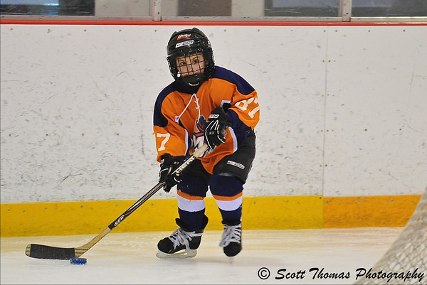 A player from one of the Mite B teams I photographed over the weekend.  The boards in a hockey rink are 42 inches (1.07 meters) in height to give you an idea of the size of this player.