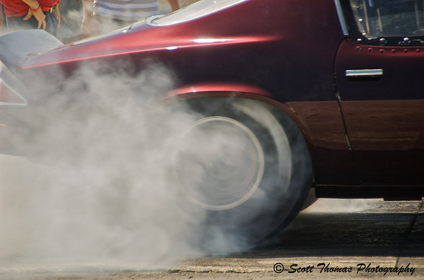 Burnout!  A Chevy Camero spins its tires in an effort to warm them up for better traction.